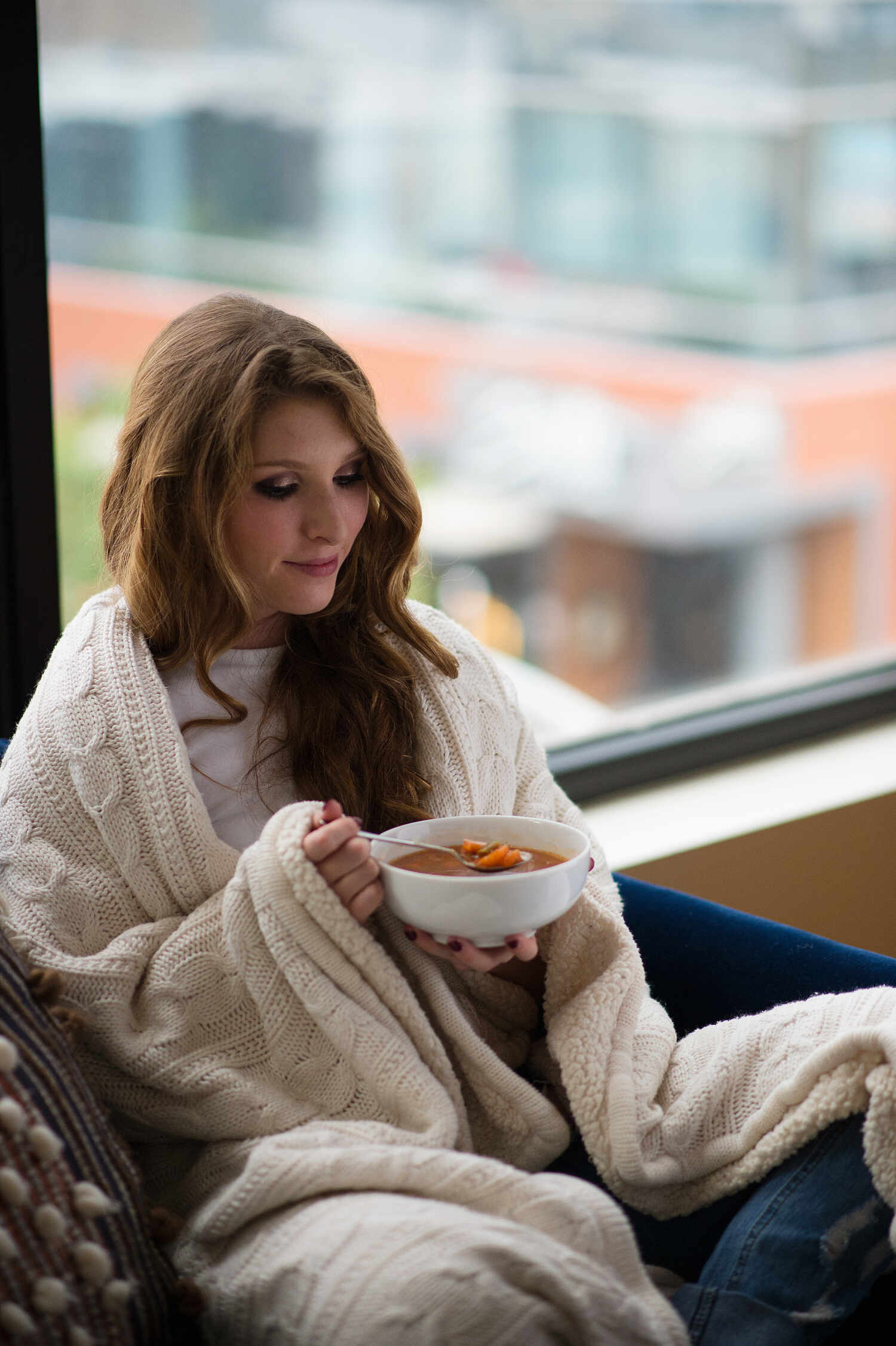 young woman eating soup in cold weather