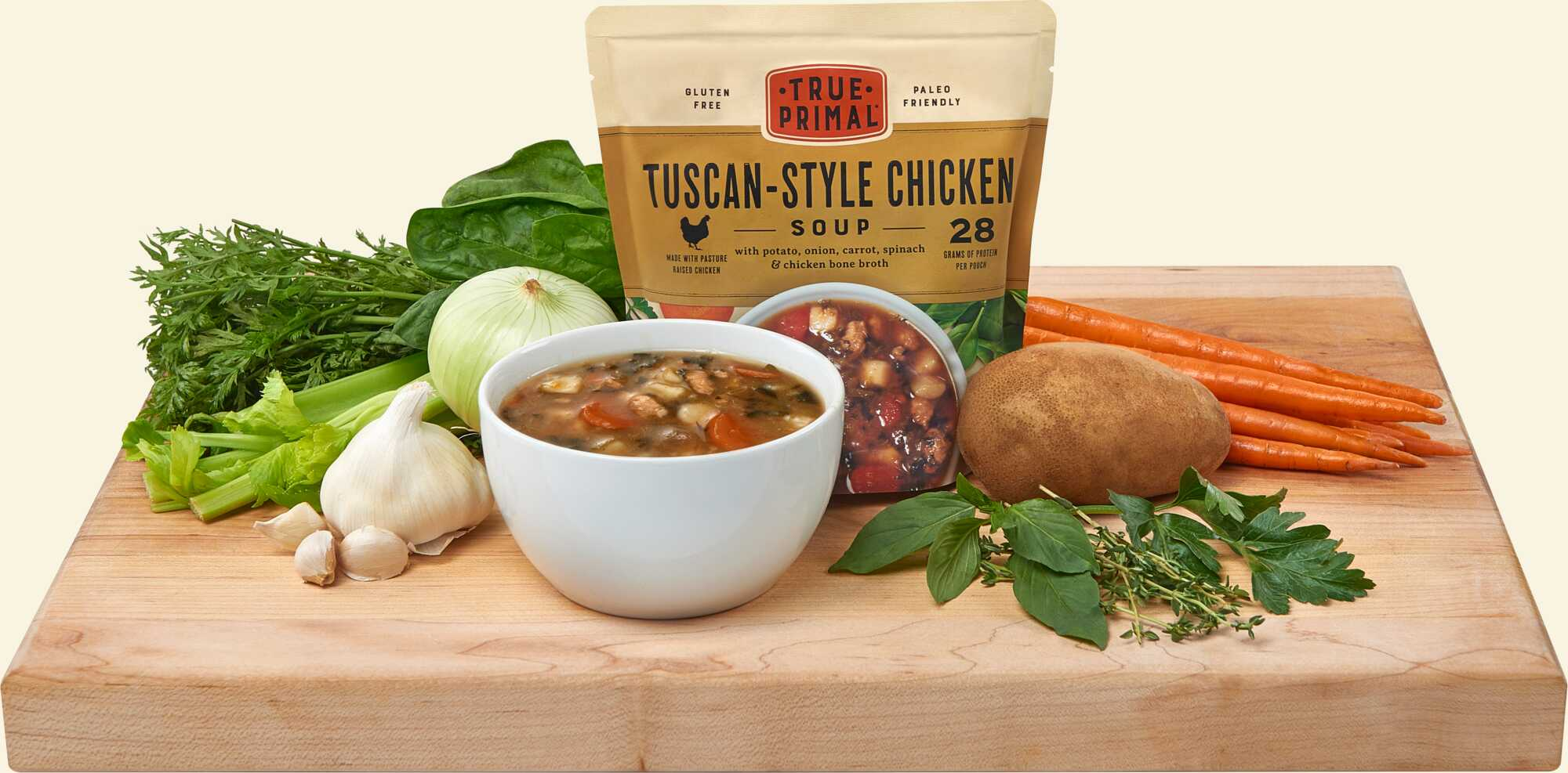 True Primal Tuscan-Style Chicken Soup on cutting board with ingredients